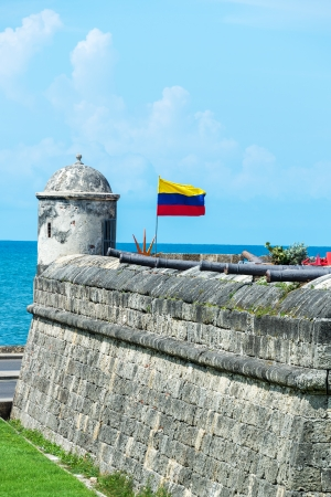 Defensive wall of Cartagena with a Colombian flag waving and several cannons visible in the old town of Cartagena, Colombia