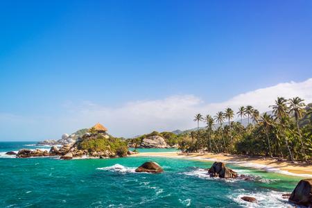 カリブ水 San Juan デル ギア コロンビアのタイロナ国立公園内のビーチでヤシの木と青
