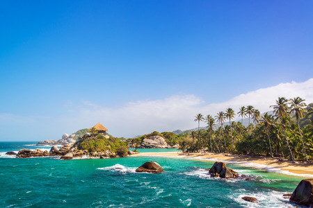 juan: Palm trees and blue Caribbean water on the beach of San Juan del Guia in Tayrona National Park in Colombia Stock Photo