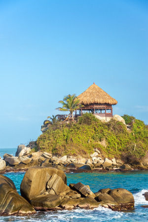Small shack with a palm tree with blue Caribbean Sea water in Tayrona National Park in Colombia 版權商用圖片