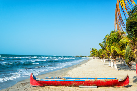 White sand Caribbean beach with a red canoe in the foreground photo