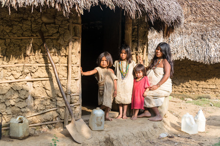 inhabits: MAGDALENA, COLOMBIA - FEBRUARY 6  An indigenous Wiwa family stands in front of their house in the Magdalena Department in Colombia on February 6, 2014   The Wiwa tribe inhabits the foothills of the Sierra Nevada de Santa Marta Mountain Range
