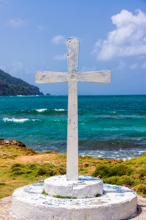 View of a white cross with the Caribbean Sea in the background at La Miel, Panama photo