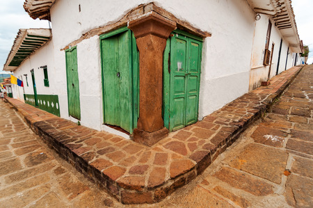 santander: Street corner with an old colonial building with green doors in Barichara, Colombia