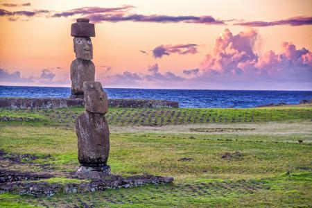 moai: Dos estatuas de Moai de la Isla de Pascua con una puesta de sol púrpura detrás de ellos