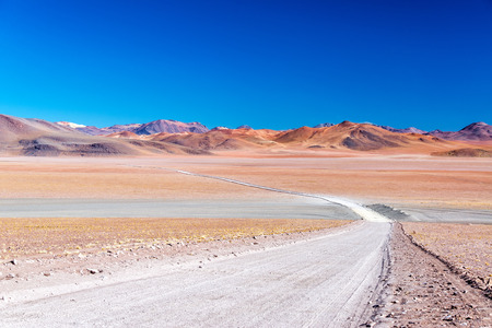 atacama: A barren yet colorful landscape with a road leading into the distance near Uyuni, Bolivia