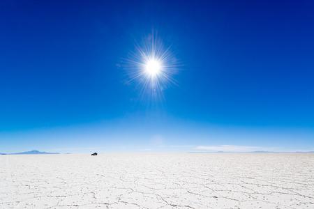 cielo despejado: Vista del sol sobre el Salar de Uyuni en Bolivia con un todoterreno en el fondo Foto de archivo