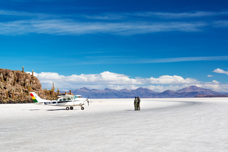 UYUNI, BOLIVIA - JULY 11   Pilots stand next to a Bolivian Air Force after landing on the Uyuni Salt Flats in Uyuni, Bolivia on July 11, 2014