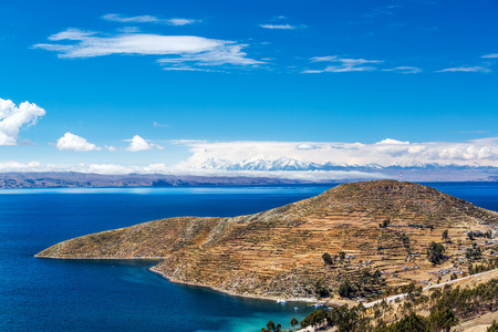 Terraced landscape of Isla del Sol with Andes mountains in the background on the Bolivian side of Lake Titicaca photo