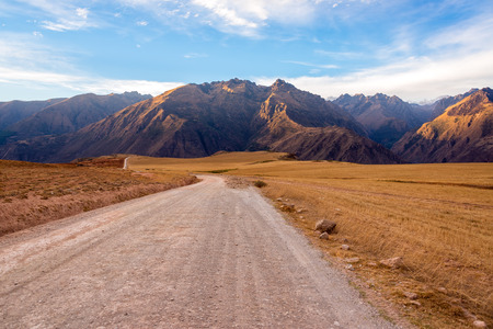 sacred valley of the incas: Dirt road with the Andes mountains rising the background in the Sacred Valley near Cusco, Peru