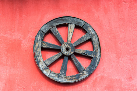 wheel house: Old wagon wheel and a red wall near Cotopaxi Volcano in Ecuador Stock Photo