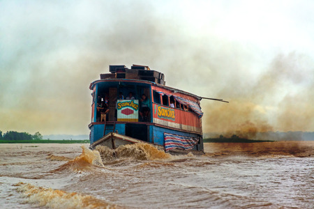 causing: IQUITOS, PERU - MARCH 11: River boat causing pollution in the Amazon River near Iquitos, Peru on March 11, 2015