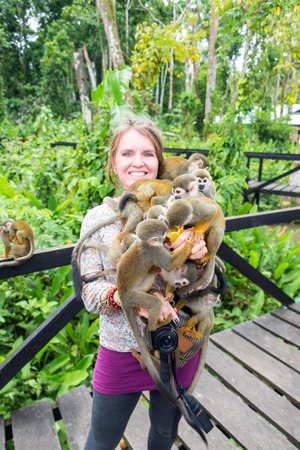 squirrel monkey: Woman holding approximately ten squirrel monkeys in Leticia, Colombia