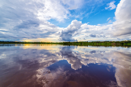 Dramatic sky reflected in the water of the Javari River in the Brazilian Amazon Stok Fotoğraf