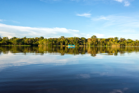 ブラジルのアマゾンの熱帯雨林で Javari 川の澄んだ青い水のジャングル、空、ボートを反映