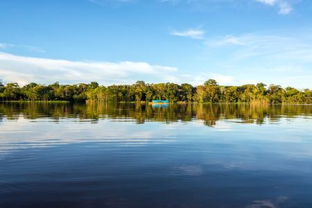브라질 아마존 열대 우림의 Javari 강 맑은 푸른 물에 반영된 정글, 하늘 및 보트 스톡 콘텐츠