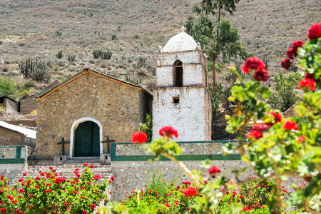 catholocism: Old colonial church inside of the Colca Canyon in Peru with flowers in the foreground