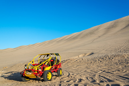buggy: Dune buggy at the foot of a large sand dune in Huacachina, Peru