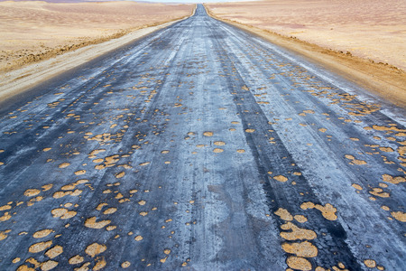 pothole: Damaged pothole filled road passing through the desert of Paracas, Peru Stock Photo