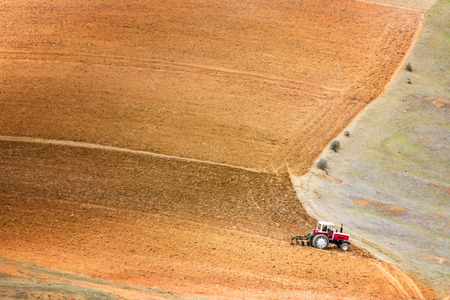 red soil: Tractor plowing a large field near Concepcion Peru