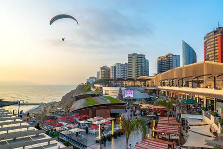 LIMA PERU  NOVEMBER 26: A paraglider flies over the Larcomar in Lima Peru on November 26 2014