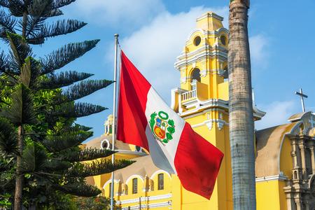 bandera de peru: Bandera peruana y la iglesia amarilla en el barrio de Barranco en Lima Perú