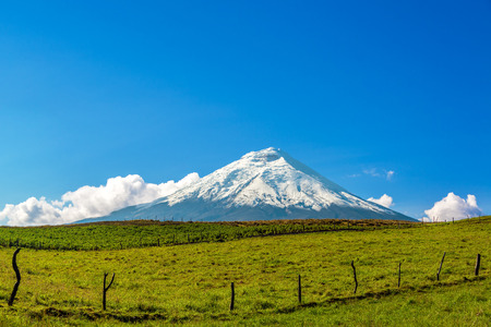 Beautiful snow capped Cotopaxo Volcano with fields in the foreground in Ecuador Stock Photo