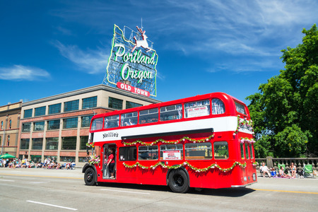 double decker: PORTLAND OR  JUNE 6: Red double decker bus passes as part of the Grand Floral Parade on June 6 2015 in Portland Oregon Editorial