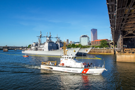 coast guard: PORTLAND OR  JUNE 7: A US Coast Guard vessel passes under the Steel Bridge in Portland Oregon during the Rose Festival on June 7 2015