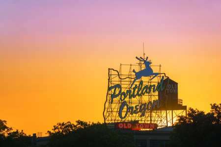 Sunset over the iconic Portland Oregon Old Town sign in downtown Portland Oregon Stock Photo