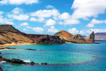 pacific ocean: View of an underwater crater in the foreground with Pinnacle Rock in the background on Bartolome Island in the Galapagos Islands Stock Photo