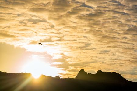 bartolome: Early morning sun coming up over hills of Bartolome Island in the Galapagos Islands in Ecuador
