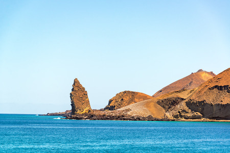 bartolome: Pinnacle Rock with the ocean and hills on Bartolome Island in the Galapagos Islands in Ecuador