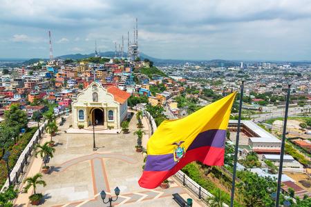 iglesia: Bandera ecuatoriana en la cima del Cerro Santa Ana con una iglesia y la ciudad de Guayaquil visible en el fondo en el Ecuador