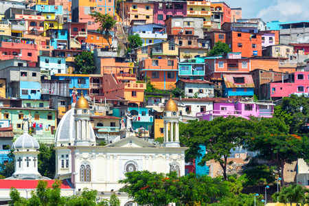 slum: White church with a colorful slum on a hill rising above it in Guayaquil, Ecuador Stock Photo