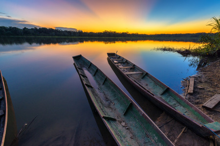 Dramatic sunset in the Amazon rain forest in Bolivia in Madidi National Park with two canoes in the foreground Stok Fotoğraf