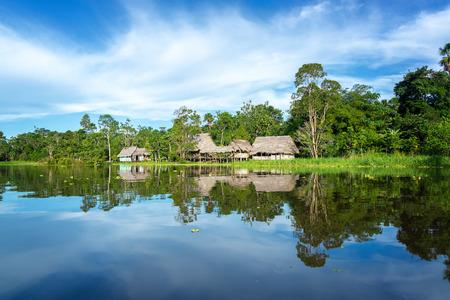 jungla: Pequeña ciudad en la selva amazónica refleja en el río Yanayacu cerca de Iquitos, Perú
