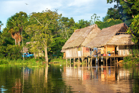 peru amazon: Late afternoon view of a shack on stilts in the Amazon rain forest with a beautiful reflection in the river