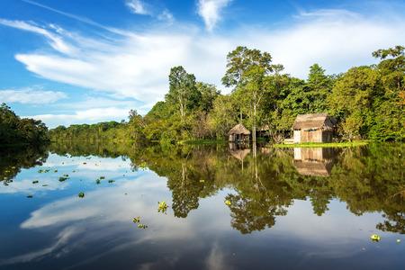 río amazonas: Pequeña choza de madera en el bosque tropical del Amazonas con una hermosa reflexión sobre el río Yanayacu cerca de Iquitos, Perú