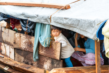 amazon rain forest: TAMSHIYACU, PERU - MARCH 11: Young child on a wooden boat in Tamshiyacu, Peru in the Amazon Rain Forest on March 11, 2015