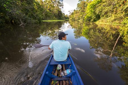 peru amazon: IQUITOS, PERU - MARCH 12: Jungle guide rowing in a canoe on the Yanayacu River near Iquitos, Peru on March 12, 2015