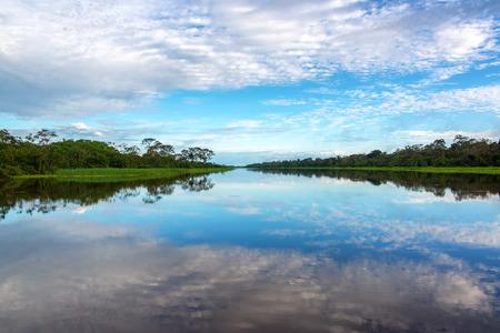 rio amazonas: Hermoso cielo se refleja en un río en la selva tropical del Amazonas en Iquitos, Perú