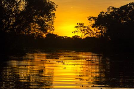 peru amazon: Fiery orange sunset on an Amazon tributary in Peru Stock Photo