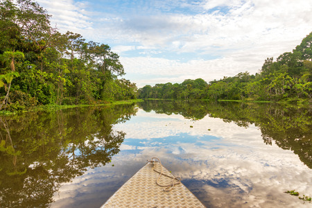 peru amazon: Front of a small boat with the sky reflected in a river in the Amazon rain forest in Peru Stock Photo