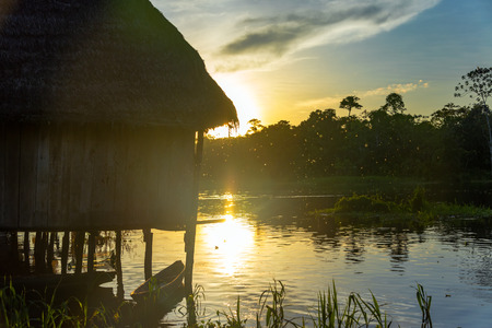 stilts: Silhouette of a shack on stilts at sunset in a village near Iquitos, Peru