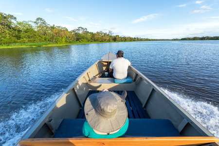peru amazon: IQUITOS, PERU - MARCH 13: Tourist and guide ride in a boat in the Amazon rain forest near Iquitos, Peru on March 13, 2015 Editorial