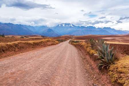 sacred valley of the incas: Dirt road leading to the Andes mountain range in the Sacred Valley of Peru