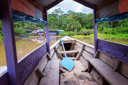 río amazonas: canoa púrpura llegar a una isla en el río Amazonas cerca de Iquitos, Perú