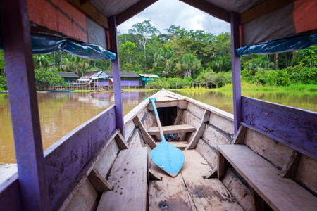peru amazon: Purple canoe arriving at an island in the Amazon River near Iquitos, Peru