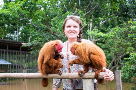 peru amazon: Tourist woman in the Amazon with two Bald Uakari Monkeys, near Iquitos, Peru Stock Photo